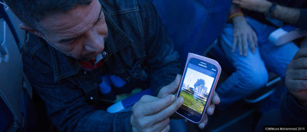 Somewhere over the Atlantic.  A Syrian refugee travelling to start a new life in Canada shows pictures of his hometown of Hama on his mobile phone. Photo: Muse Mohammed / IOM.