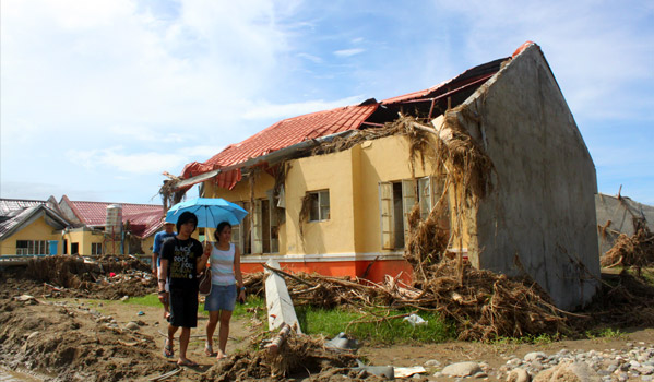 Residents of Iligan City in Southern Philippines walk past damaged houses from the flash floods last December 2011. © IOM 2012 (Photo by: Friena Guerrero)