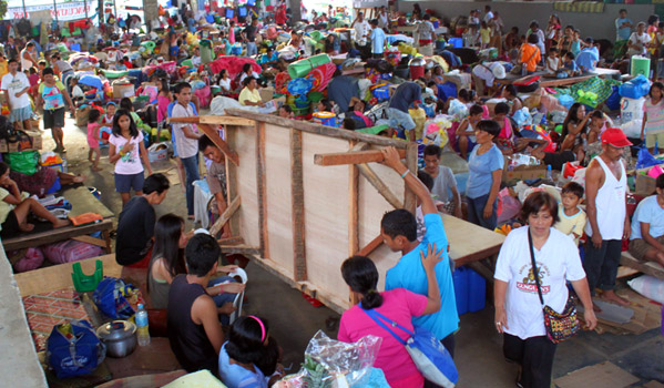 IOM staff distribute bed kits to families inside an evacuation centre in Cagayan de Oro City in Southern Philippines. © IOM 2012 (Photo by: Friena Guerrero)