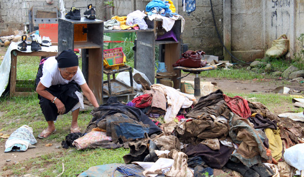 An elderly lady fixes flooded items in Balulang in Cagayan de Oro. © IOM 2011 (Photo by: Friena Guerrero)