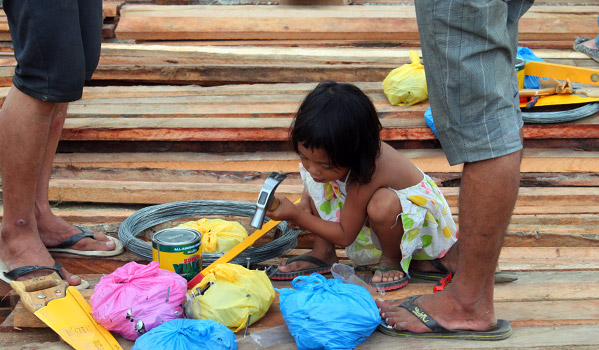 A child plays around with the shelter repair kits that IOM distributed to families in Cagayan de Oro. © IOM 2011 (Photo by: Friena Guerrero)