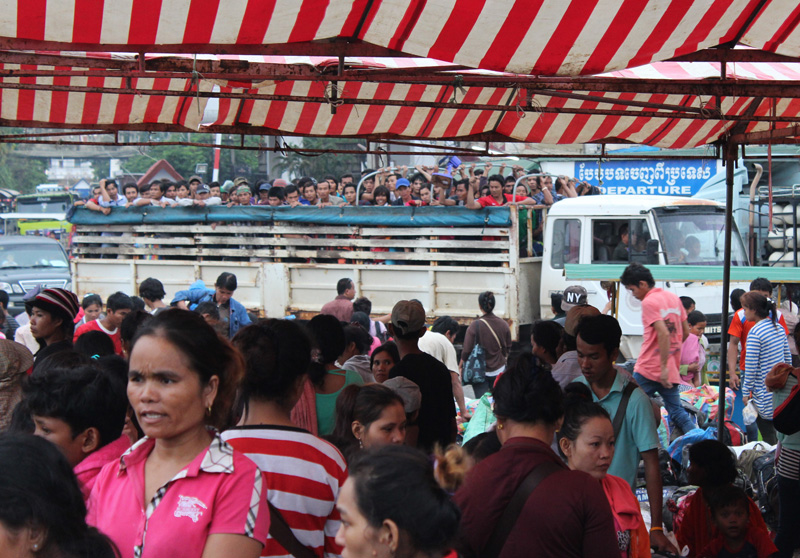 A truckload of returning migrants at Poi Pet  passes others waiting for onward transport. © IOM 2014 (Photo by Joe Lowry)