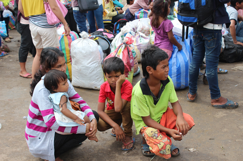 Cambodian migrant family waiting for transportation to their home village at Poi Pet border crossing at the weekend. © IOM 2014 (Photo by Joe Lowry)