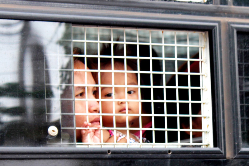 A Cambodian mother and child look out of a police van on arrival at Poi Pet, Cambodia. © IOM 2014 (Photo by Joe Lowry)