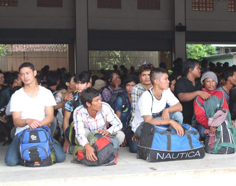 Undocumented Cambodian migrant workers wait at Anranya Prathet, Thailand prior to onward transportation to the border. © IOM 2014 (Photo by Joe Lowry)