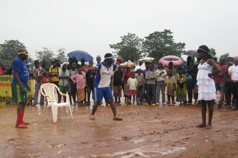 """The community theatre performance incorporated members of the comedians association and local residents. The play is called """"Travaillons en unite pour la cohesion sociale à Miskine"""" and was written by the performers in coordination with IOM. The play had a message of peace and reconciliation, and accepting difference among all Central Africans. © IOM 2014 (Photo by Nina Papachristou)"""