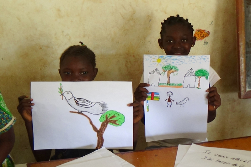 """Many children drew birds of peace, while others drew their own homes, always including a Central African flag. The children also wrote songs about peace, and one group performed a song at the """"Mega-Concert"""" in the fifth district on August 30. © IOM 2014 (Photo by Nina Papachristou)"""