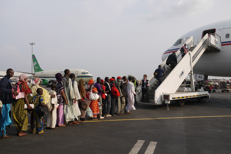 Chadian brothers wait for their flight home. IOM helped 314 Chadians leave the Central African Republic (CAR) and flew them back to Chad. This was the 19th evacuation flight conducted by IOM for Third Country Nationals (TCNs) exiting CAR. © IOM 2014 (Photo by Sandra Black)