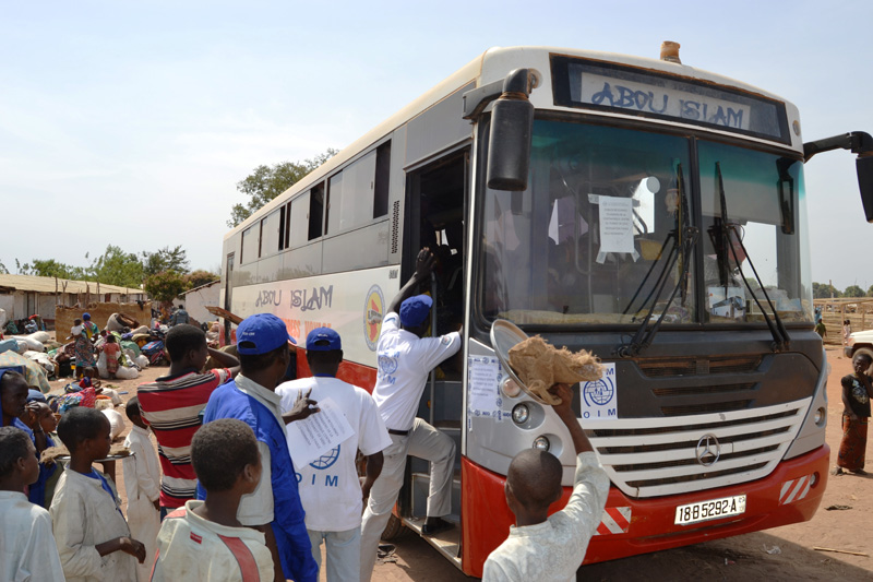 An IOM bus departing from the border area Sido with Chadian returnees bound for N'Djamena. © IOM 2014 (Photo by Craig Murphy)