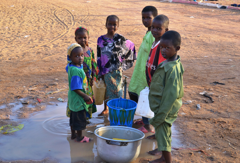 Children collecting tap water at the Doba transit site. © IOM 2014 (Photo by Craig Murphy)