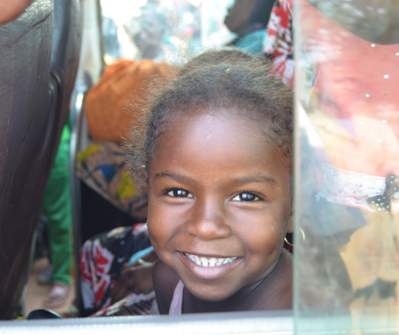 A young girl smiles in an IOM bus departing from Doba to N'Djamena, the final destination. © IOM 2014 (Photo by Craig Murphy)