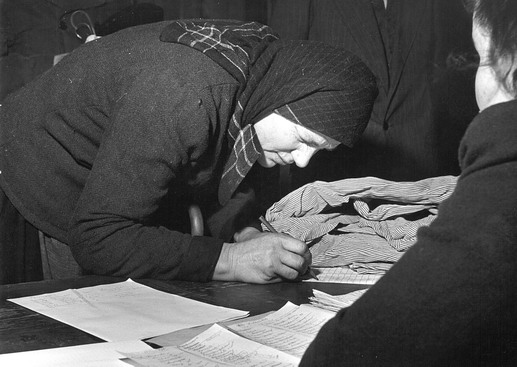 An older escapee registers with an ICEM official. Photo © IOM 1958 – HAT0194