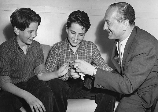 Gabor (left) and Stefan Forbath, smile happily as their father present them with new watches as they arrive in Sydney. Their father, Imre Forbath, is a Sydney businessman. Photo © Australian Official Photograph 1956 – HAU0308 – T. Hood