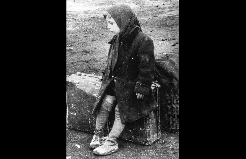 This tiny Hungarian girl sits with all her family cound carry pictured shortly after crossing Austrian border. Photo ©Herald Tribune United Press 1956 – HAT0182