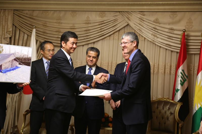El Viceministro de Relaciones Exteriores del Japón, Sr. Nobuo Kishi (a la izquierda), entrega un certificado al Jefe de Misión de la OIM en el Iraq, Sr. Mike Pillinger (a la derecha), para dar constancia del donativo de 800 tiendas de campaña y 10.000 bidones a refugiados sirios en el Iraq. © OIM 2014