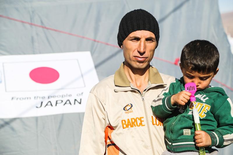Unos refugiados sirios en el campamento de Basirma, establecido en la provincia de Erbil, en la región septentrional del Iraq, recibieron tiendas de campaña y otros artículos de primera necesidad donados por el Gobierno del Japón. © OIM 2014
