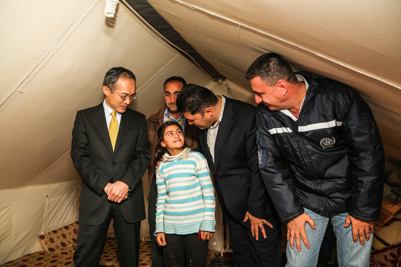 El Embajador Masato Takaoka habla con refugiados para conocer de primera mano las condiciones en el campamento de Basirma y sus experiencias. © OIM 2014