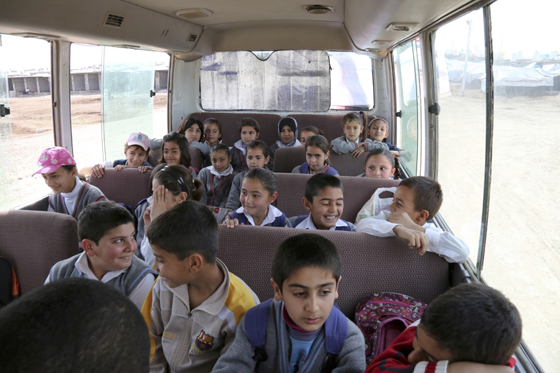 Hundreds of Syrian families living in camps have faced difficulties sending their children to school. To address this concern, IOM organized a transport initiative where fleets of school buses bring children to school everyday. Before the transportation initiative was launched, many children had no choice but to stay at home. © IOM 2014