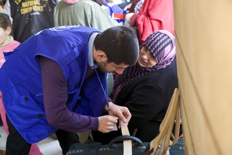 IOM Operations staff placing tags on passengers' bags during embarkation.