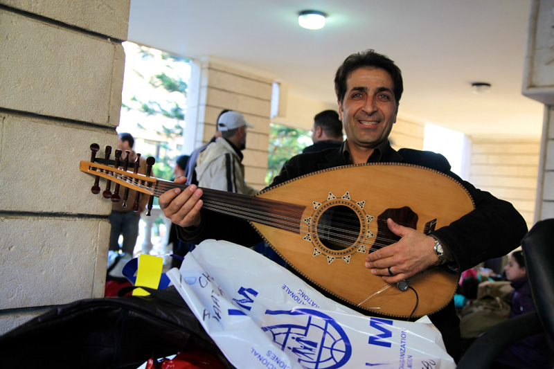 "This man travelling from Syria with his wife, son, and daughter made sure not to leave behind his most valuable possession, a traditional ""oud"" instrument, a reminder of his Syrian heritage. © IOM 2014 (Photo: Remi Itani)"