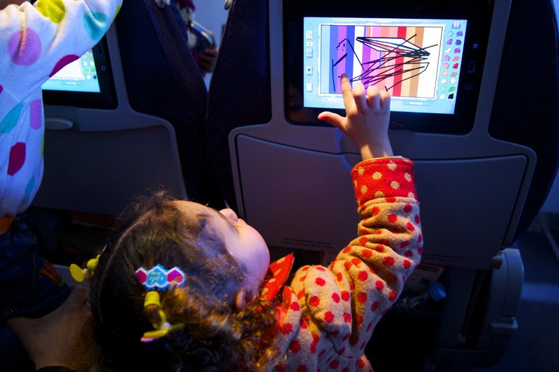 "On the plane, children have fun with the ""AirBerlin"" in-flight entertainment, while their parents get some rest. © IOM 2014 (Photo: Remi Itani)"