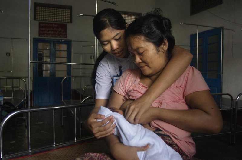 "Promoting Safe Delivery: ""I am 41, this is my first baby. I was told at the village by the young volunteer I could get good health care here at the hospital, so I decided to come for my first visit 7 months ago and came back 3 more times. Everything went well."" Daw Mar Mar Htay, mother of a 4-day-old child, Ka Don Ka Ni Station Hospital, Bogale Township © IOM 2013 (Photo by Valeria Turrisi)"