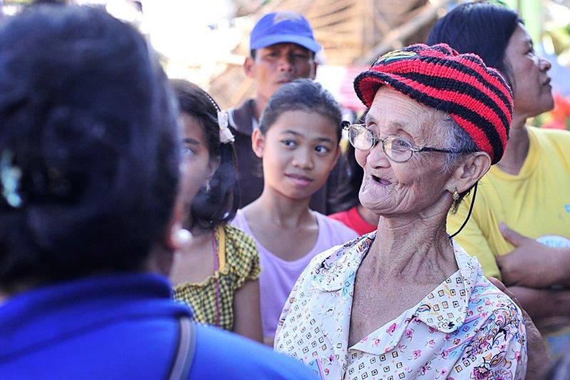 Una mujer de 78 años comunica sus inquietudes al equipo de evaluación de la OIM y OMS en Pontevedra, Capiz. © Blue Motus 2013
