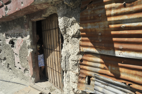 A resident peeks out from her house, which still bears bullet and mortar holes a year after the clashes between the Government troops and separatist rebels in Zamboanga City. © IOM 2014 (Photo by Alan Motus)