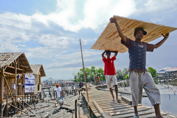 """The houses were built, using materials supplied by IOM, by people whose livelihoods had been affected by the conflict – many of them future residents.  Participants in the """"Buggoc challenge"""" were paid a daily wage, and were supported with guidance from IOM, the local government and  the Department of Social Welfare and Development (DSWD).  Civic organizations and private groups have also generously supported the initiative with donations.  © IOM 2014 (Photo by Ray Leyesa)"""