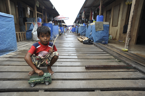A boy plays outside a bunkhouse at Mampang transitional site, where over 500 families – roughly 2,700 people – are currently temporarily housed.  © IOM 2014 (Photo by Alan Motus)