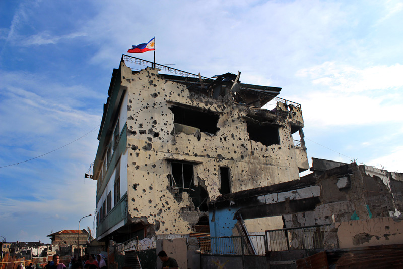 The Philippines national flag flies above a heavily-damaged building in Santa Catalina, Zamboanga, the scene of fierce fighting between Government troops and MNLF rebels in September. © IOM 2013 (Photo by Joe Lowry)