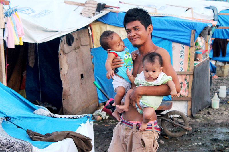 A young father with his two small children outside their shelter in the Joaquin F Enriquez Memorial Stadium in Zamboanga. © IOM 2013 (Photo by Joe Lowry)