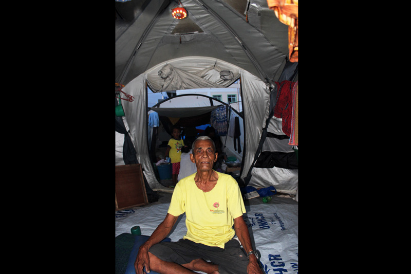 An old man sits under an IOM-donated solar lamp in a makeshift camp at the Cawa Cawa seafront in Zamboanga, Southern Philippines where tens of thousands of people are still displaced, two months after heavy fighting paralyzed the city. © IOM 2013 (Photo by Joe Lowry)