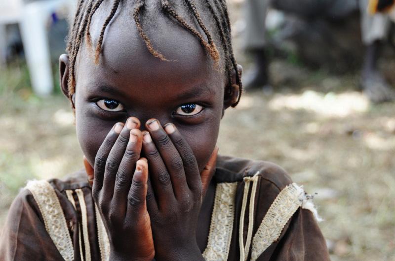 Una joven sonríe disimuladamente mientras aguarda con su familia para inscribirse como pasajeros del viaje hacia Torit (Equatoria Oriental).  La OIM brinda asistencia a los migrantes vulnerables y desamparados que han retornado a Sudán del Sur para llegar sus destinos finales.  El equipo médico de la Organización evalúa la salud de los retornados 72 horas antes de la salida del viaje. © OIM 2012