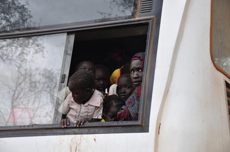 Una mujer y sus hijos asomados a la ventanilla del autobús que les lleva al campamento para refugiados de Batil.  La OIM ha colaborado con el ACNUR en la reubicación de 18.000 refugiados desde Kilo 18, un centro de tránsito a escasos kilómetros de la frontera con Sudán.  Los refugiados pasan más de dos semanas caminando antes de cruzar la frontera con Sudán del Sur, a donde llegan en busca de alimentos, seguridad y refugio. © OIM 2012