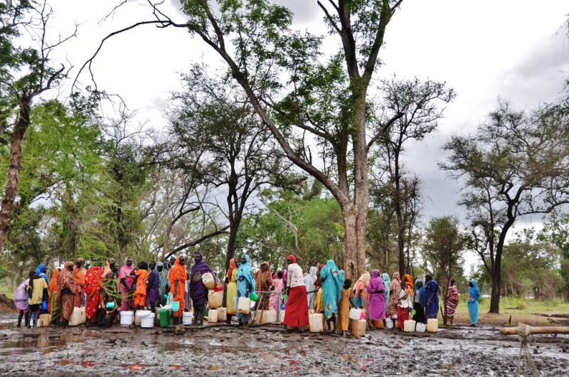 Imágenes de un punto de abastecimiento de agua en el campamento de refugiados de Batil, en el condado de Maban, estado del Alto Nilo (Sudán del Sur), donde se reparten 13 litros de agua diarios por persona.  La OIM colabora con los socios dedicados a las labores de agua y saneamiento, a quienes presta material.  El tanque de la foto es un T45 y tiene una capacidad de 45.000 litros.