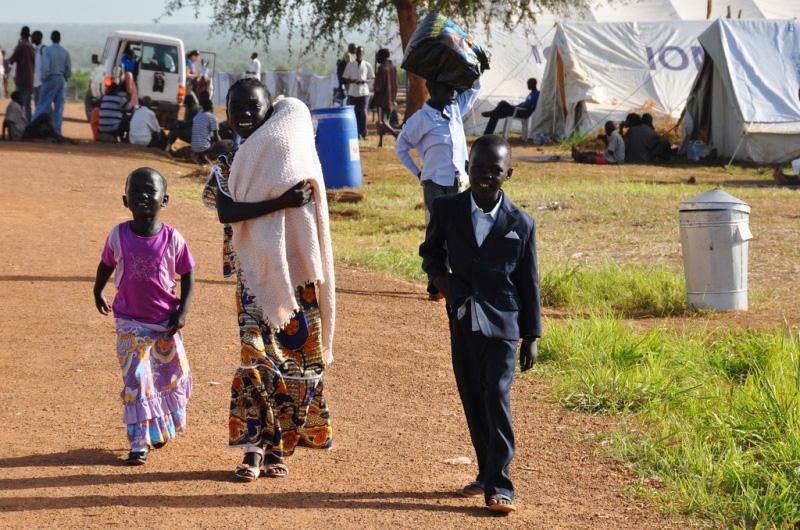 Unos niños avanzan con entusiasmo hacia el lugar desde donde partirá un convoy con destino a Torit (Equatoria Occidental).  La OIM ha organizado 5 convoyes en los que 3.454 retornados alojados en el centro de tránsito han viajado hacia 7 estados de Sudán del Sur. © OIM 2011