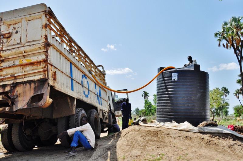 La OIM transporta agua en camiones a las aldeas remotas del campamento de Doro, donde residen más de 42.000 refugiados.  Asimismo, debido a la dificultad de acceso durante la temporada de fuertes lluvias, ha distribuido más de 400 filtros de agua y perfora cuatro pozos para asegurarse de que el abastecimiento de agua de los residentes de zonas remotas no dependa de la llegada de los camiones. © OIM 2011