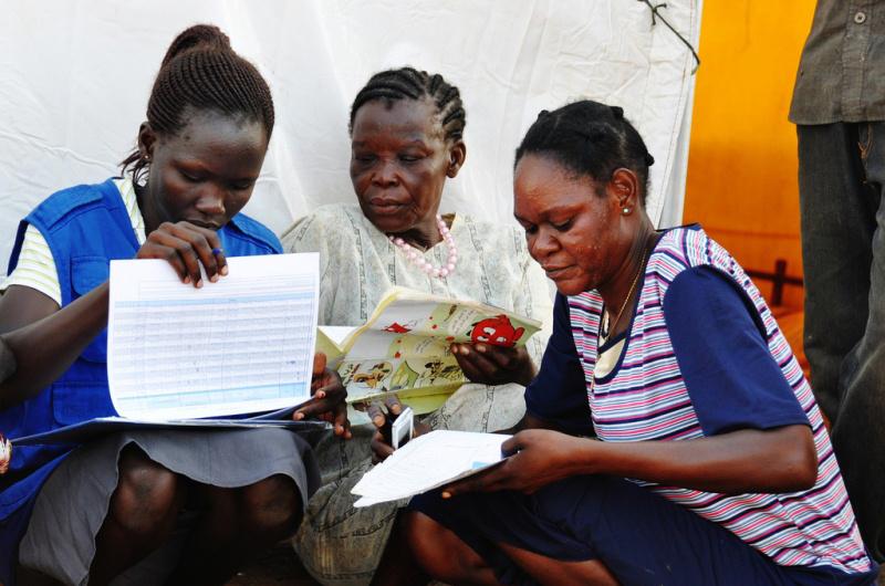 La OIM gestiona una base de datos sobre los retornos a Sudán del Sur.  Además, cuenta con una red de más de 500 empadronadores a nivel nacional, encargados de registrar y supervisar los retornos al país.  En la imagen, trabajadores de la Organización cotejan los documentos con los manifiestos originales de los vuelos durante un ejercicio de verificación de la población en el centro de tránsito para retornados de Juba. © OIM 2011