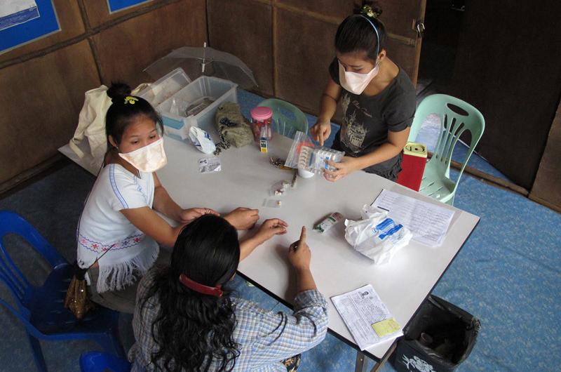 DeeDee, intérprete de la OIM, con un enfermo de tuberculosis en un puesto sanitario del campamento Mae Lat. © OIM 2012