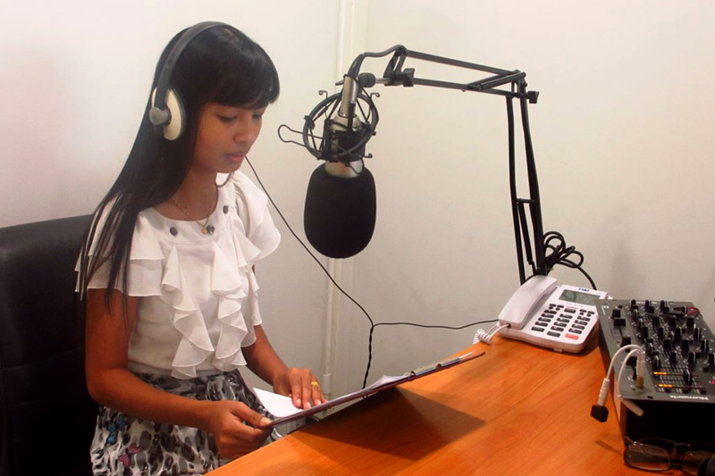An IOM field staff in Phang Nga conducts a live radio broadcast about Malaria in two languages, Burmese and Thai. © IOM 2014