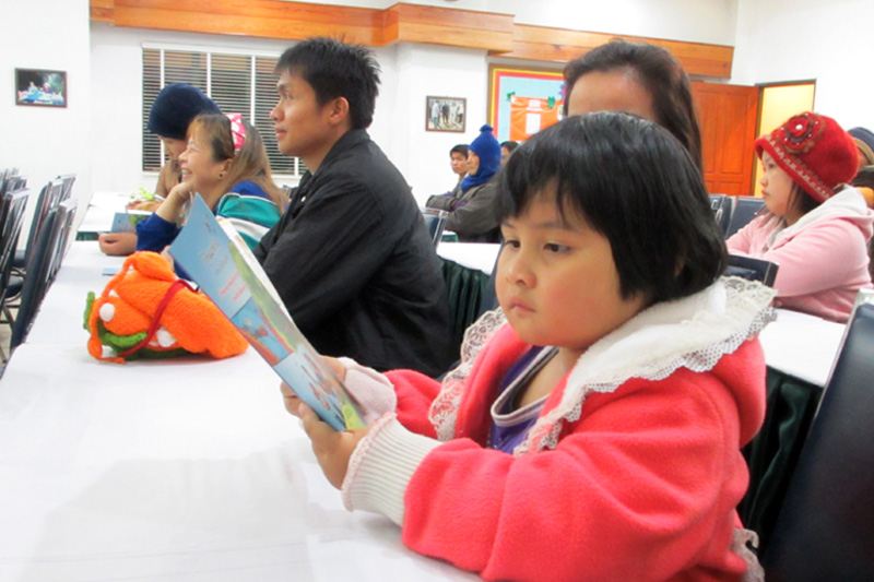 A migrant girl reads a comic book about Malaria during a workshop in Chiang Mai. © IOM 2014