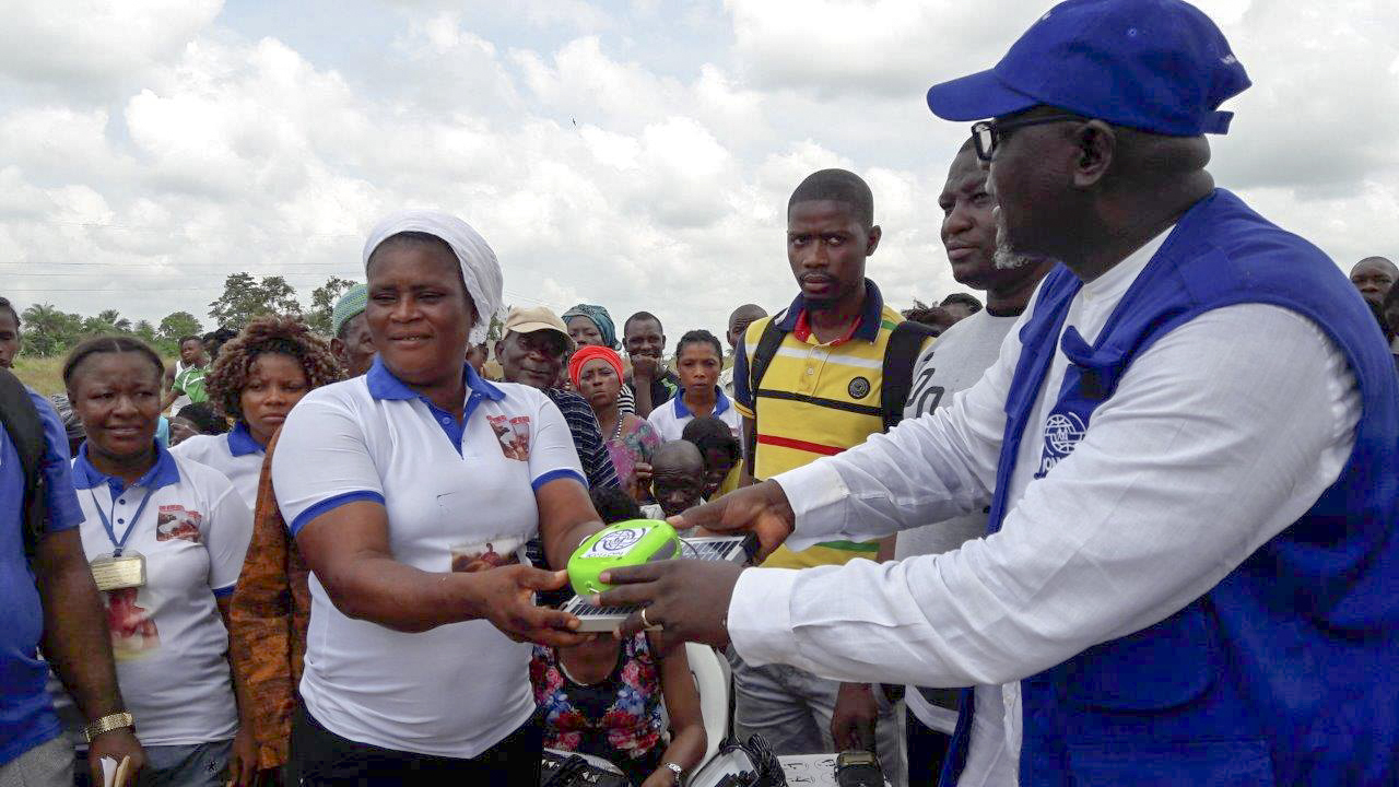 At the donation ceremony in Sierra Leone, a local resident receives a Panasonic solar lantern as part of the IOM's Global Solar Lanterns Initiative. Photo: IOM