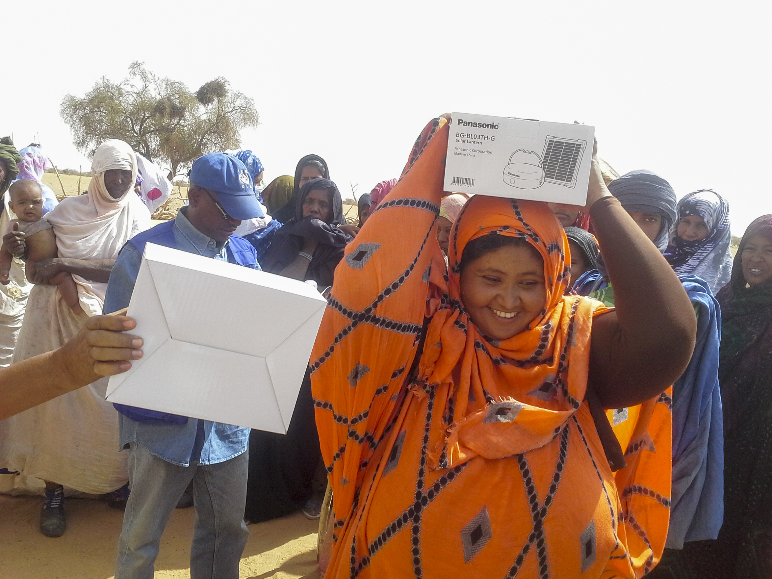 A Mauritanian woman rejoices after receiving a Panasonic solar lantern kit. Photo: IOM