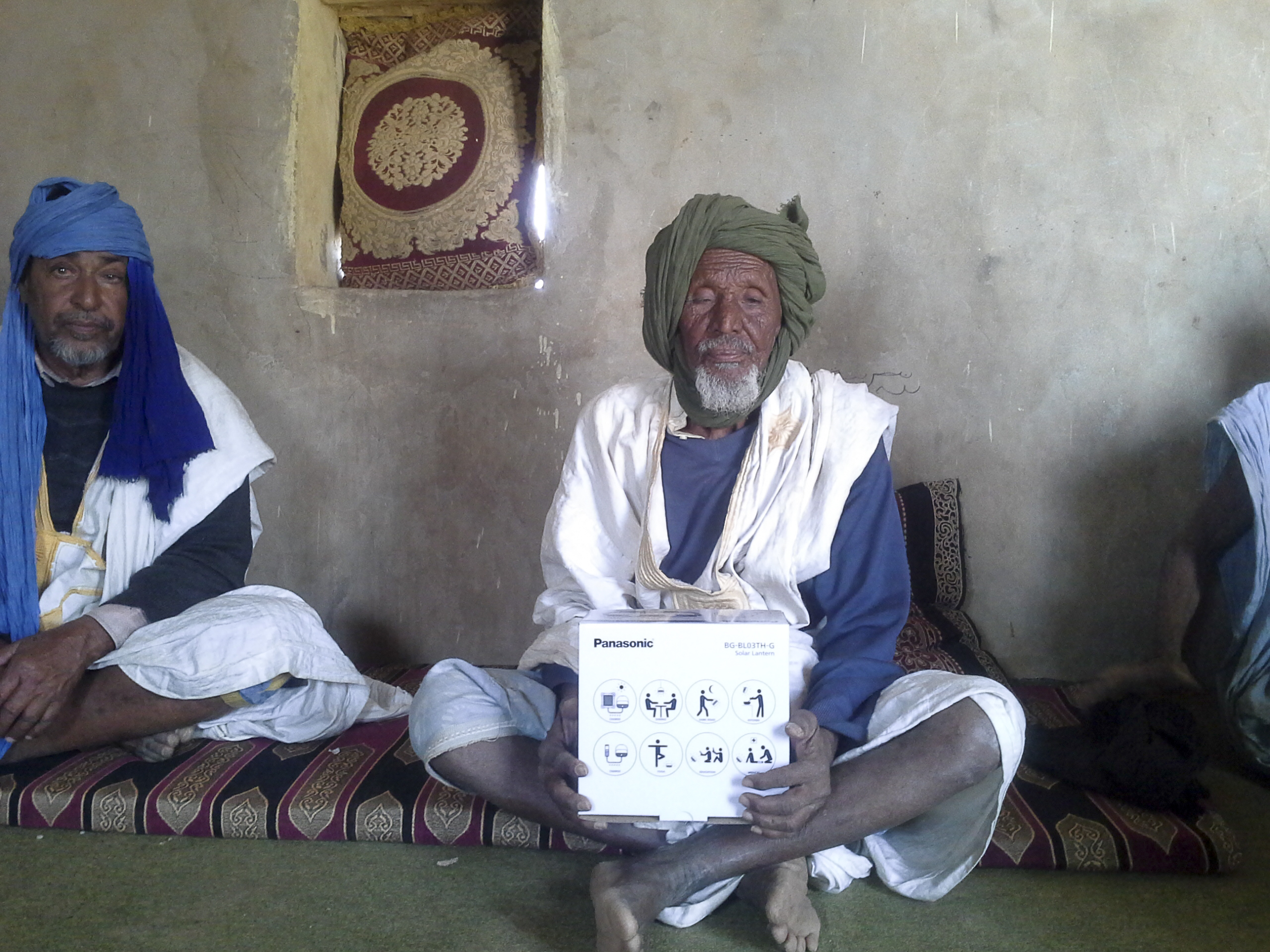 An elderly man with a Panasonic solar lantern in his home in Mauritania. Photo: IOM
