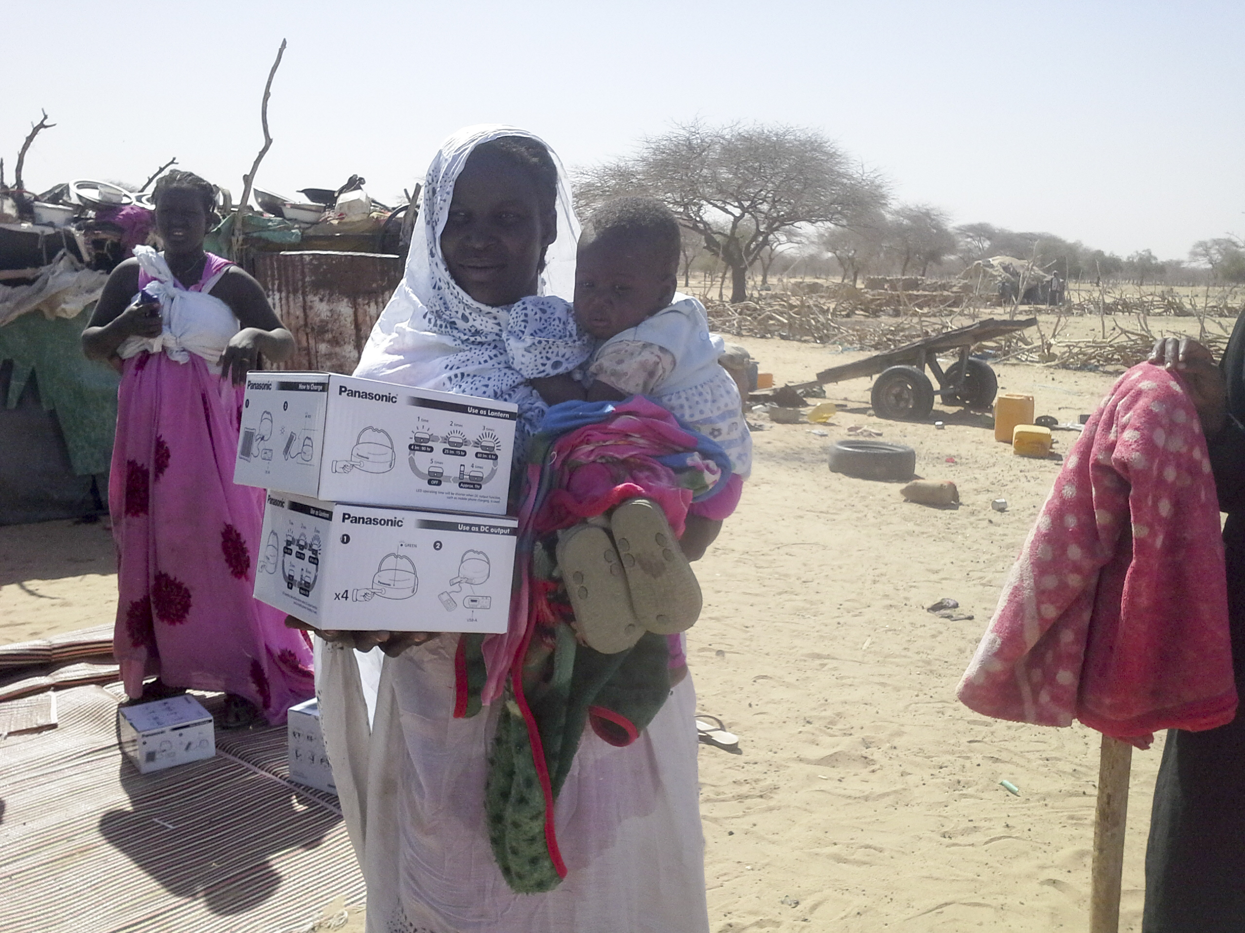 A mother and child receive two Panasonic solar lanterns in a remote region of Mauritania. These solar lanterns allow women to spend the night without fear of danger. Photo: IOM