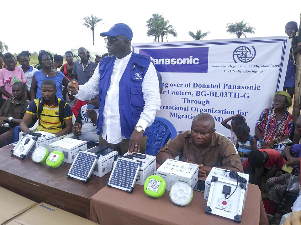 An IOM staff member organizes the distribution of Panasonic solar lanterns for flood victims in Sierra Leone. © IOM