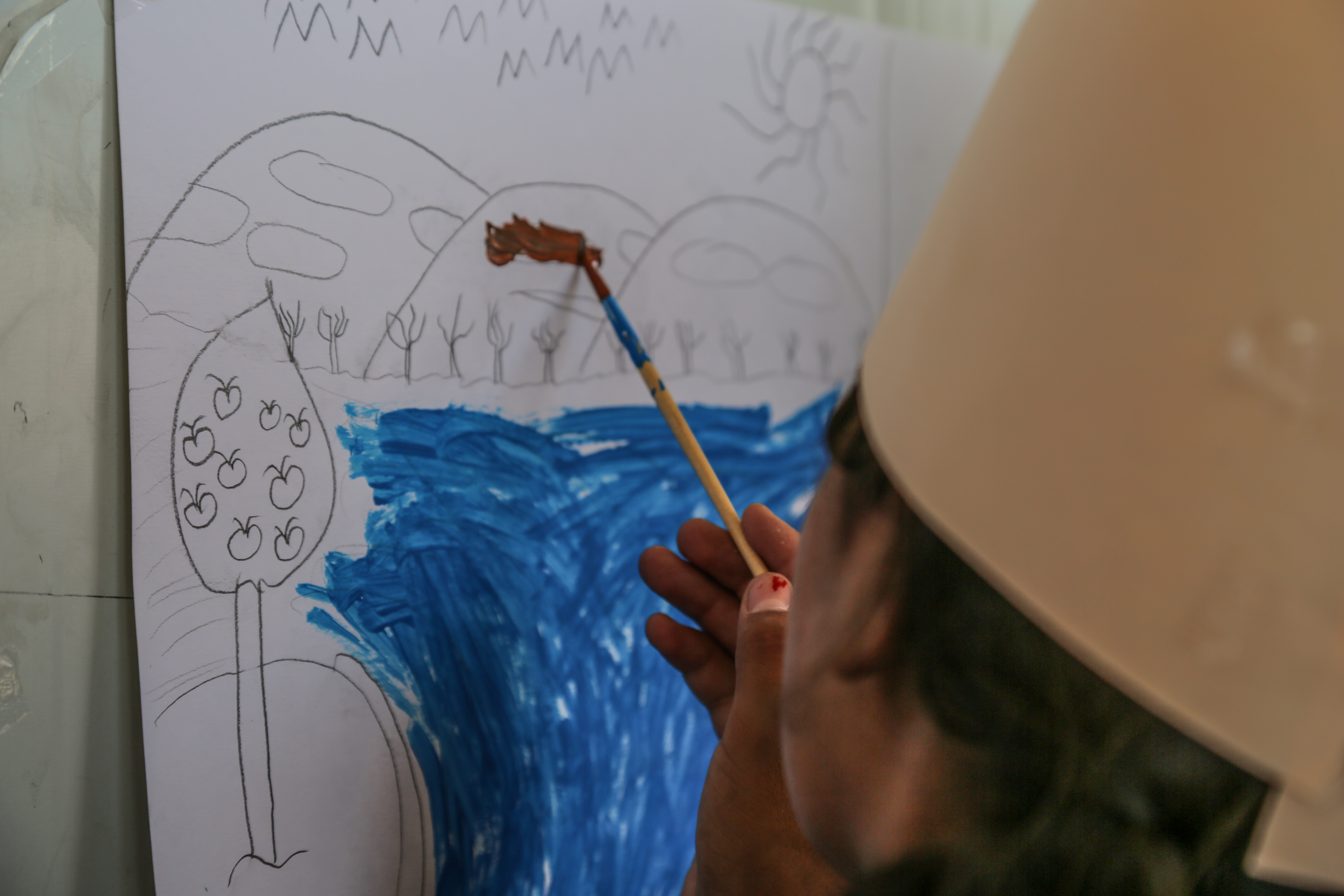 A displaced Iraqi child at IOM's psychosocial center at Chamakor camp, for displaced Iraqis, engaged in drawing activities.