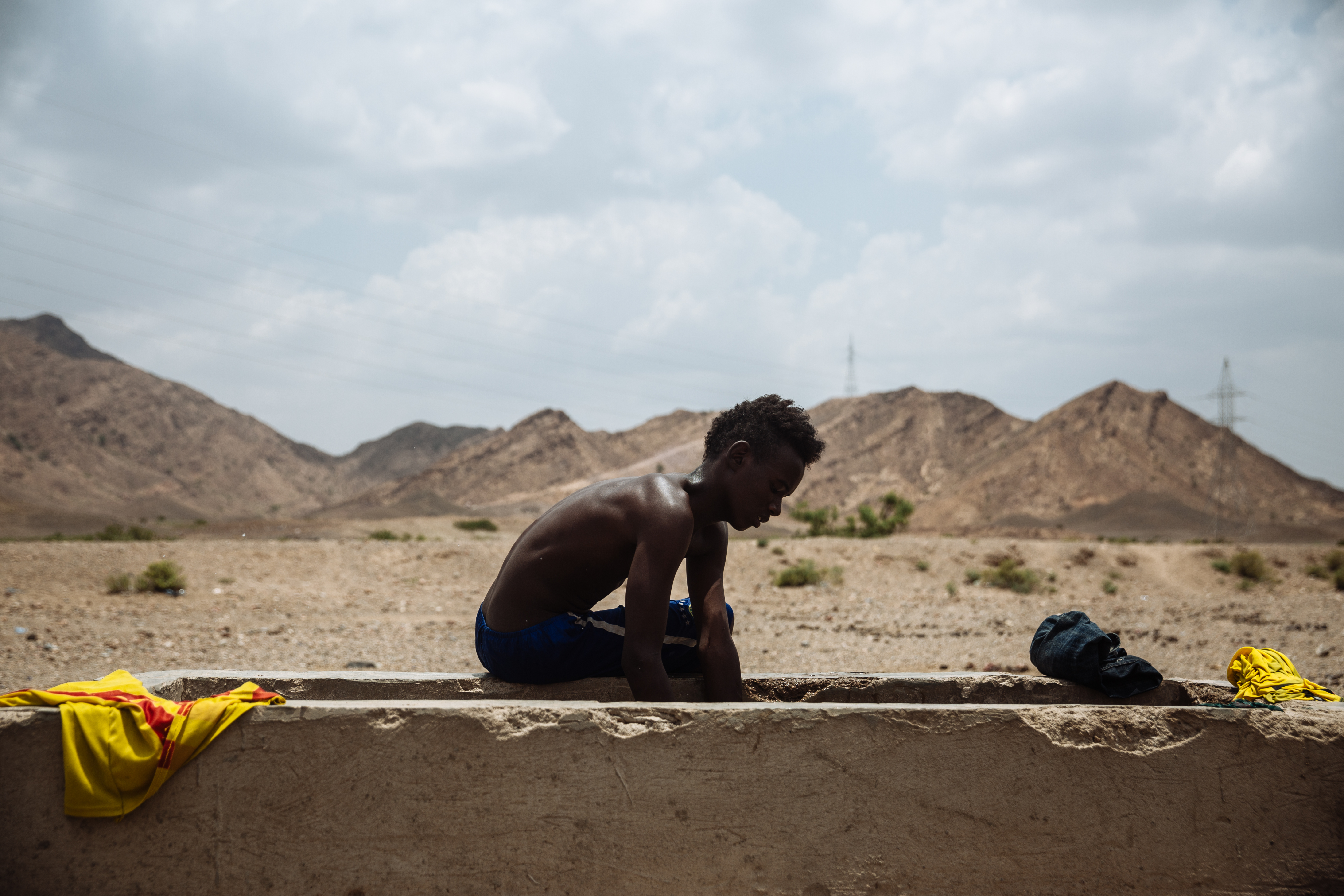 Ahmed washes his clothes at a well in Ali Sabieh. Just 14 years old, he left his village in the Oromo region of Ethiopia to be able to make more money for himself.