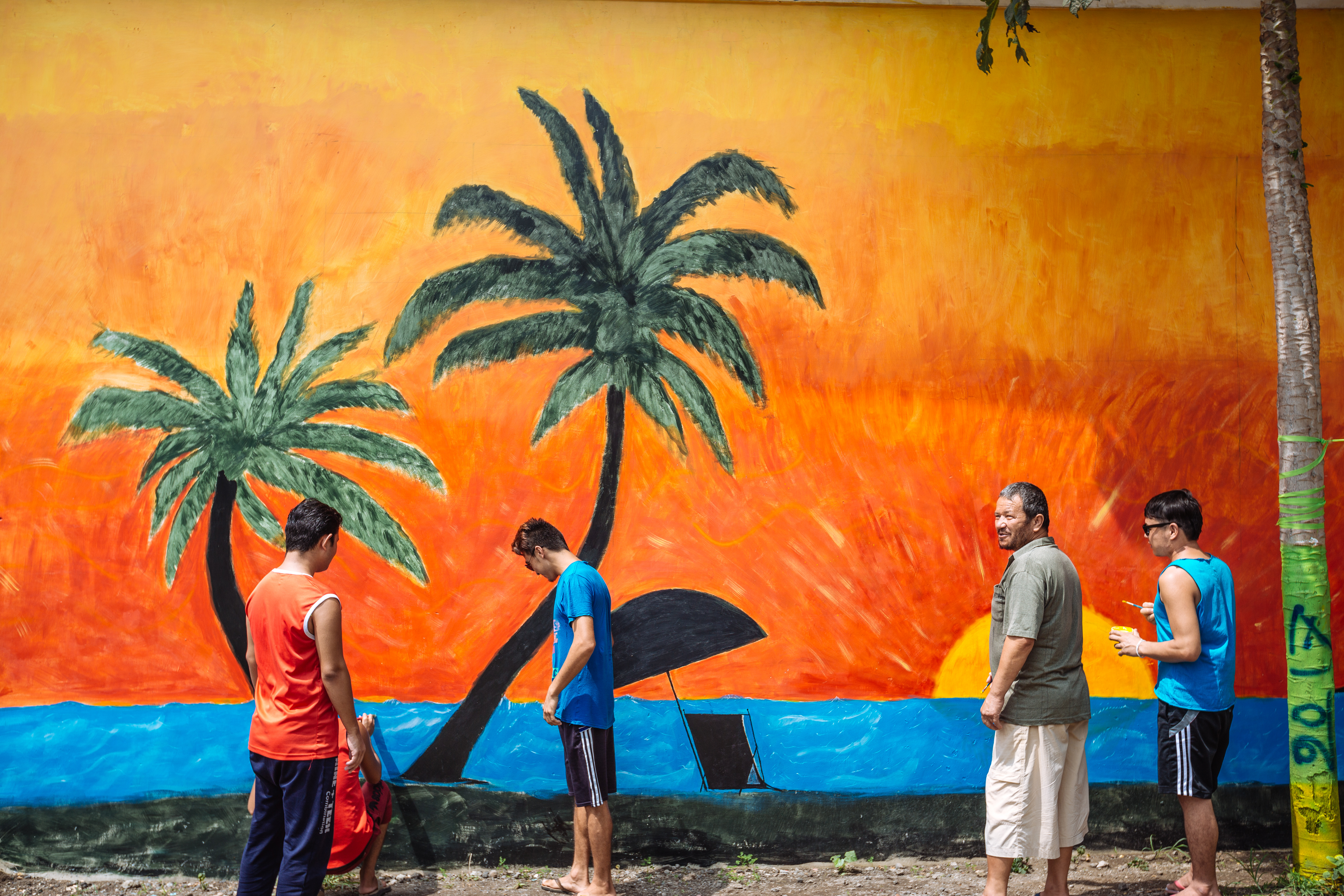 Refugees take time and make a mural within the detention centre as part of a social cohesion activity. Until the day comes for them to be resettled, they try to keep their spirits up through various recreational activities.